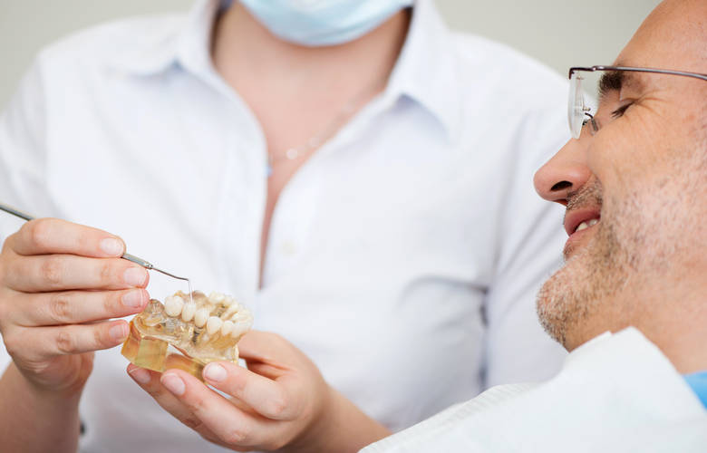οδοντίατρος εξηγεί σε ασθενή γ ια την τεχνητή οδοντοστοιχία